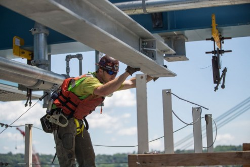 June 7, 2016 - An ironworker helps guide a new section of main span steel to its final position.