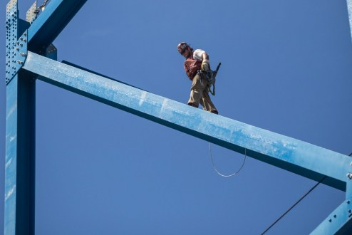 June 22, 2016 - An ironworker ascends a new, temporary support tower that will rise 150 feet above the river.