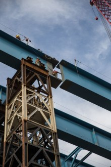 March 15, 2016 – Crew members help guide a massive steel girder to its final position.