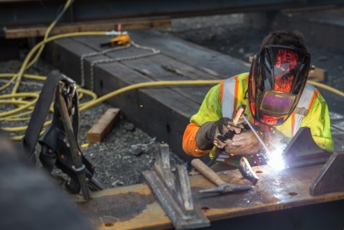 September 30, 2015 - An ironworker welds materials for a support track near the Westchester abutment.