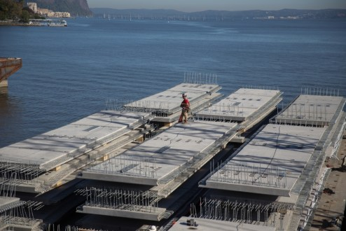 October 12, 2015 - These steel-reinforced concrete panels rest on a nearby barge before they are raised into place to form the new bridge's road deck.