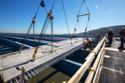 October 12, 2015 - Workers make final adjustments as a high-strength road deck panel is positioned for the new bridge.