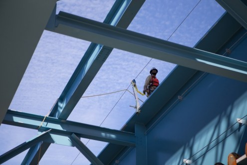 June 17, 2015 - An ironworker utilizing a safety harness atop the new bridge's first girder assembly.