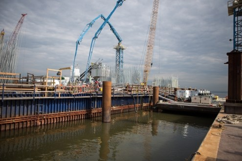 June 30, 2015 - Two of the project's floating batch plants deliver a steady supply of concrete to the main span foundations.