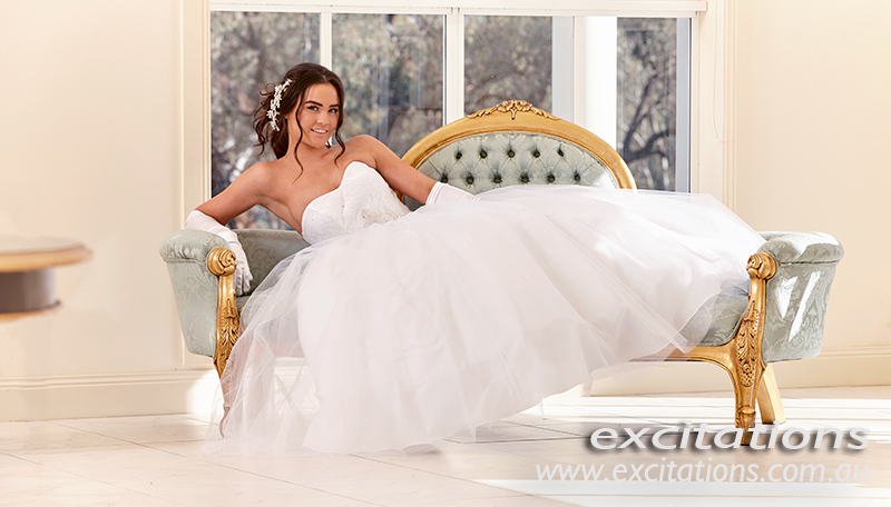 Beautiful debutante reclying on antique furniture in a large white ballroom. High key debutante photography on location by Excitations, photographers Sunraysia, Australia.