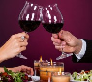 Smiling Couple Tossing Wine Glass While Having Dinner