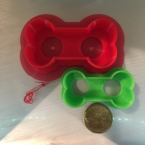 Two 3D printed dog bone shaped cookie cutters and a $1.00 loonie coin for size comparison