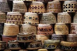 Ein Stapel Kummas: Kumma, so heißt die tradtitionelle Kopfbedeckung der Männer im Oman. Foto: www.nikkiundmichi.de