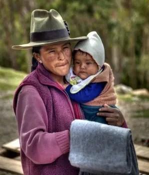 Eine Quechua-Frau hält ihr Kind im Arm.