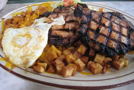 Grilled pork chops, papitas and a fried egg