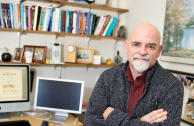 Psychology professor John Coley sits in his office