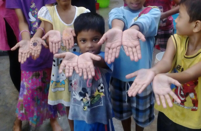Children show their clean hands after practicing proper hand washing skills.