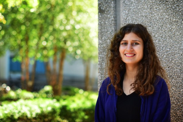 Raina Levin stands in front of a wall on Northeastern University's campus