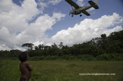 A Huaorani child watches as Alas de Socorro takes off from the grass strip runway.