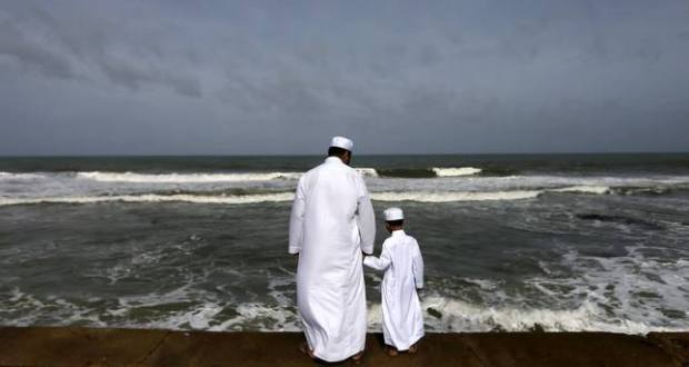 A Sri Lankan Muslim father and son stand in front of the sea during morning prayers of Eid al-Fitr celebrations marking the end of Ramadan, in Colombo