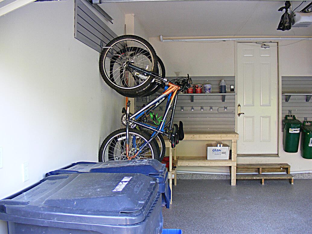 Garage organized with slatwall bicycle rack hooks, a custom-built ...