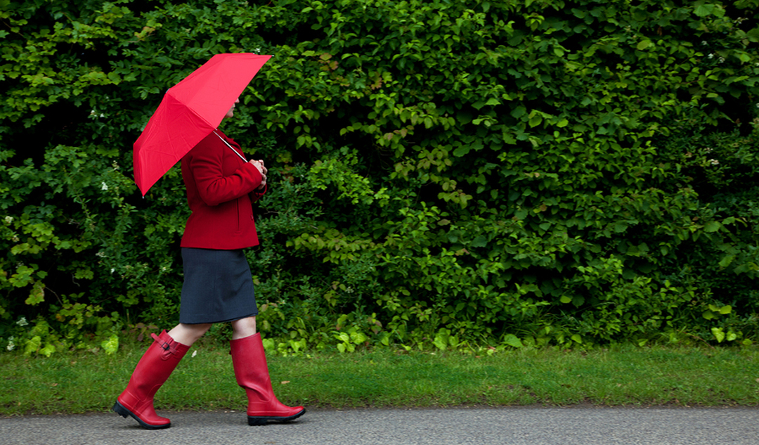 Photo of a woman in red walking along a road with her umbrella u