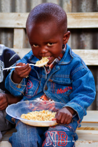 African boy eating food Kenya Nyumbani