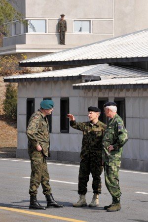 """Brigadier General Andrzej Przekwas from Poland, Major General Jean-Jacques Joss from Switzerland and Major General Christer Lidstrom from Sweden talk as a North Korean soldier (top) stands guard before a meeting of the Neutral Nation Supervisory Commission (NNSC) at the truce village of Panmunjom in the demilitarized zone dividing two Koreas on April 8, 2009. North Korea warned of """"strong steps"""" if the United Nations censures its rocket launch, hours after releasing triumphal footage of what Pyongyang describes as a peaceful space programme."""