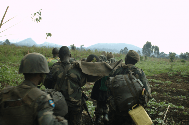 FARDC infantry carry an injured man a couple of hundred meters from the front line on a makeshift stretcher. Very rudimentary medicine — a tourniquet for his gunshot leg and an injection for pain relief. They had to carry him around three kilometers back to where the doctor tended to him (Photo: Joseph Kay).