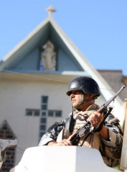 An Iraqi police commando stands guard outside the Virgin Mary church in Baghdad on November 5, 2010 as Iraqi forces impose heavy security measures following the October 31 deadly hostage drama inside a church in the war-torn capital. (Photo: Ahmad al-Rubaye/AFP/Getty Images).