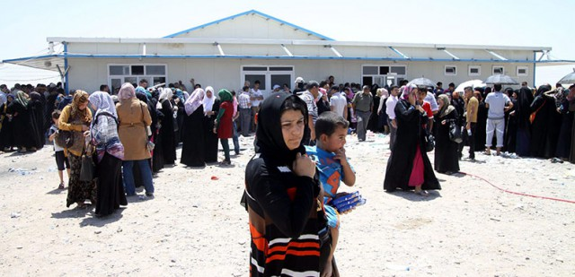 Iraqis who fled the violence in Mosul wait at a checkpoint in Erbil, Kurdistan region, north Iraq, 11 June 2014.
