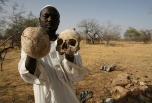 Darfur survivor Ibrahim holds human skulls at the site of a mass grave where he says the remains of 25 of his friends and fellow villagers lie, on the outskirts of the west Darfur town of Mukjar (Source: Nassar Nassar/AP, 23.04.2007).