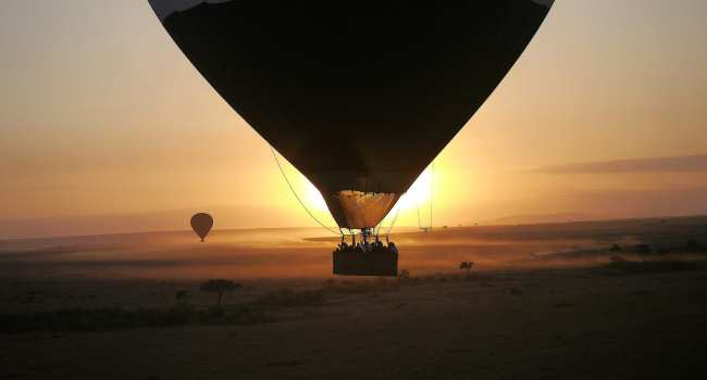 """Hot air balloon against sunrise at Masai Mara"""