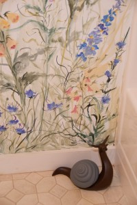 large wooden snail in bathroom with hand-painted garden mural