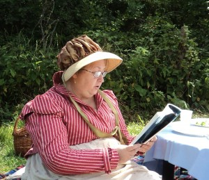 Woman seated at a piucnic reading aloud from a book