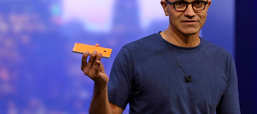 "Microsoft CEO Satya Nadella holds a Nokia Lumia mobile phone during address at the company's  ""build"" conference in San Francisco"