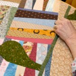 A crazy quilt, already pieced together, is quilted by hand.