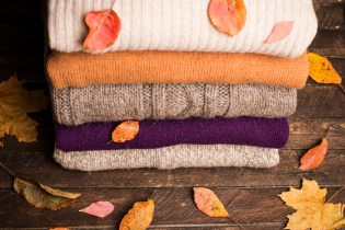 Knitted winter clothes on wooden background covered with autumn leaves, knitwear, space for text. Stack of knitted sweaters and cardigans.