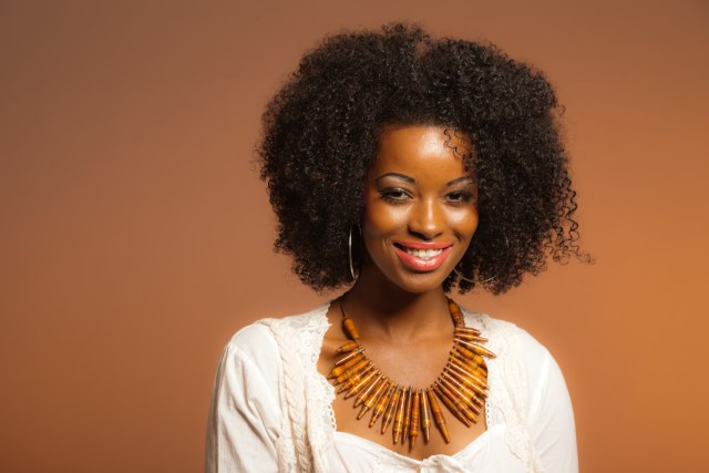 Vintage 70s fashion afro woman. White shirt and jeans against brown background.