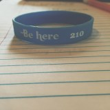 """Photo of Emily Pedone's bracelets supporting her suicide prevention club. The cause is called """"Be210""""."""