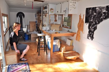 Renee Couture sits inside her studio with the summer evening sun streaming in through the open door and windows./Sabina Poole