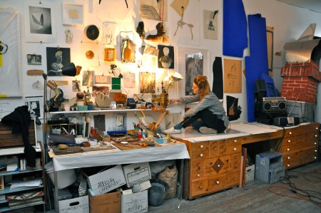 Blair sits comfortably on any surface in her workspace, it is like a theatrical home for her.
