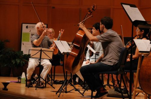 """Violinist Theodore Arm (left) discusses David Schiff's new arrangement of """"Peer Gynt"""" during rehearsal. Photo: Kimmie Fadern/Chamber Music Northwest"""