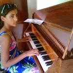 Practicing her recital piece on a harpsichord.