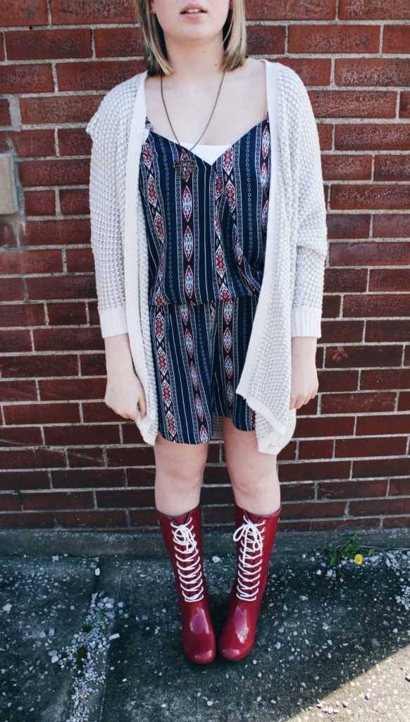 Clothes for a cause. Modeling a printed romper, silver cardigan, and lace-up Roma boots.