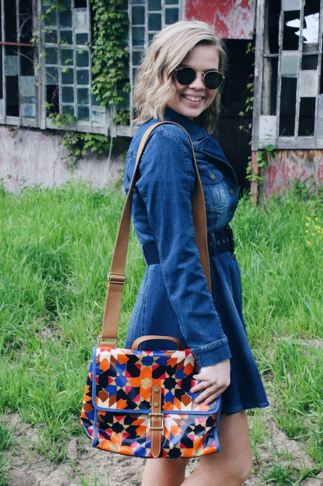 I'm Feeling Inspired By The 70s. Close up of the pleated denim dress, round Ray-Ban sunglasses, and a printed Fossil purse.