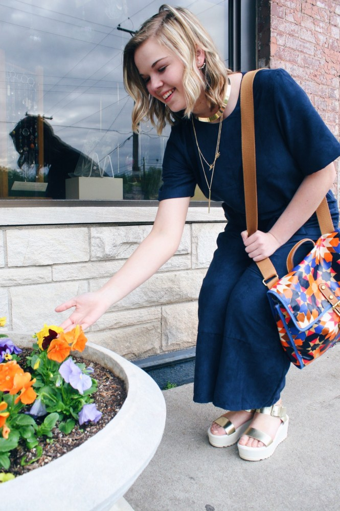A Jumpsuit and a CEO Trade Show. Looking at flowers in a navy jumpsuit, platform sandals, gold jewelry, and printed Fossil purse.