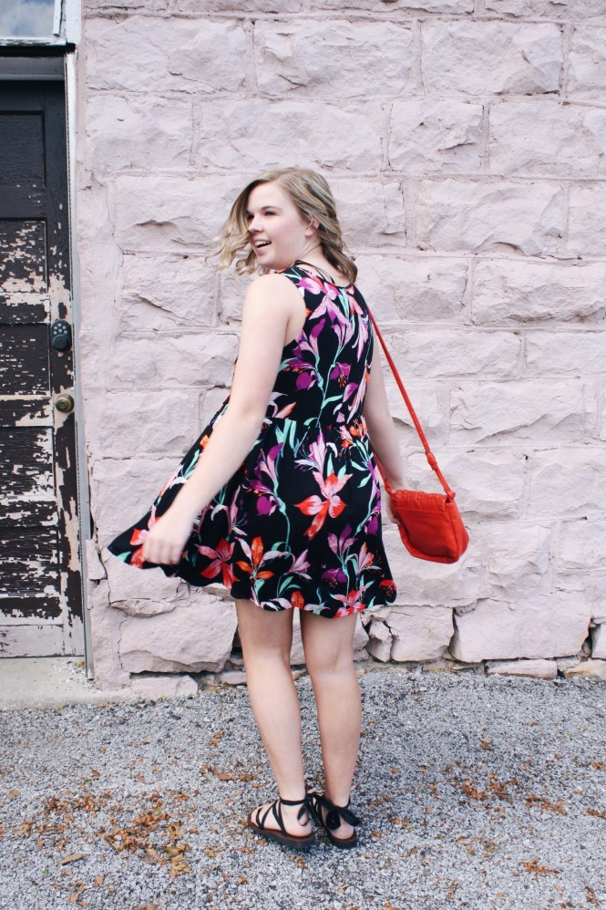 It's All In The Details. Back of the floral printed dress, orange cross body purse, and lace-up Sseko sandals.