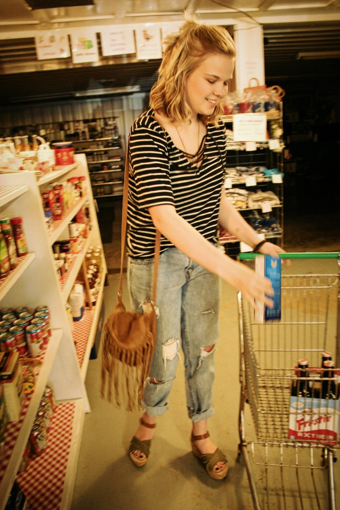 Celebrity Inspired Clearance Rack Finds. Grocery shop modeling in a striped lace up tee, distressed boyfriend skinny jeans, platform sandals, a fringe cross body, and gold jewelry.