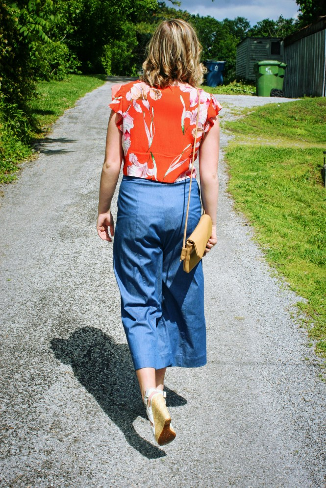 Being Bold In Floral, Blue, & Gold. Modeling a floral crop top, denim flare pants, gold accessories, wedges, and a neutral cross body.