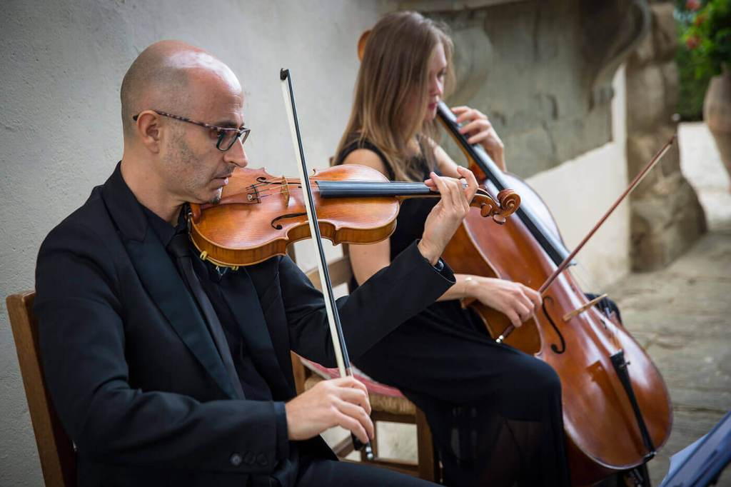 a string duo play during the reception