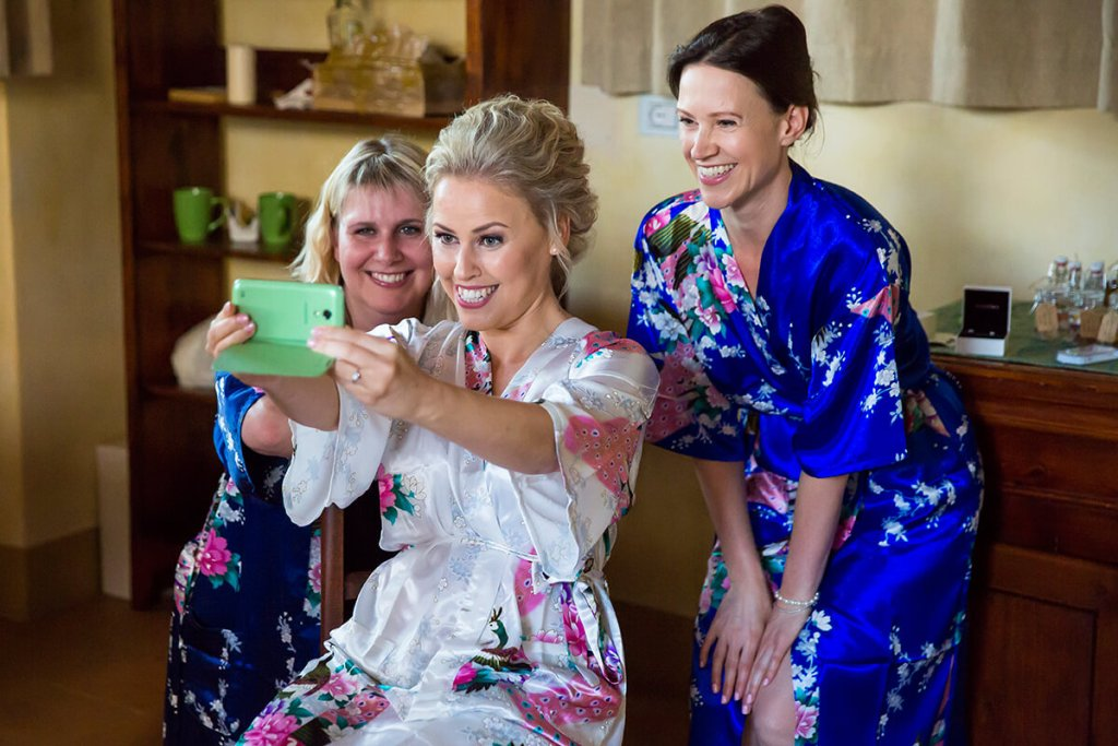 the bride snaps a selfie with the bridesmaids before the ceremony