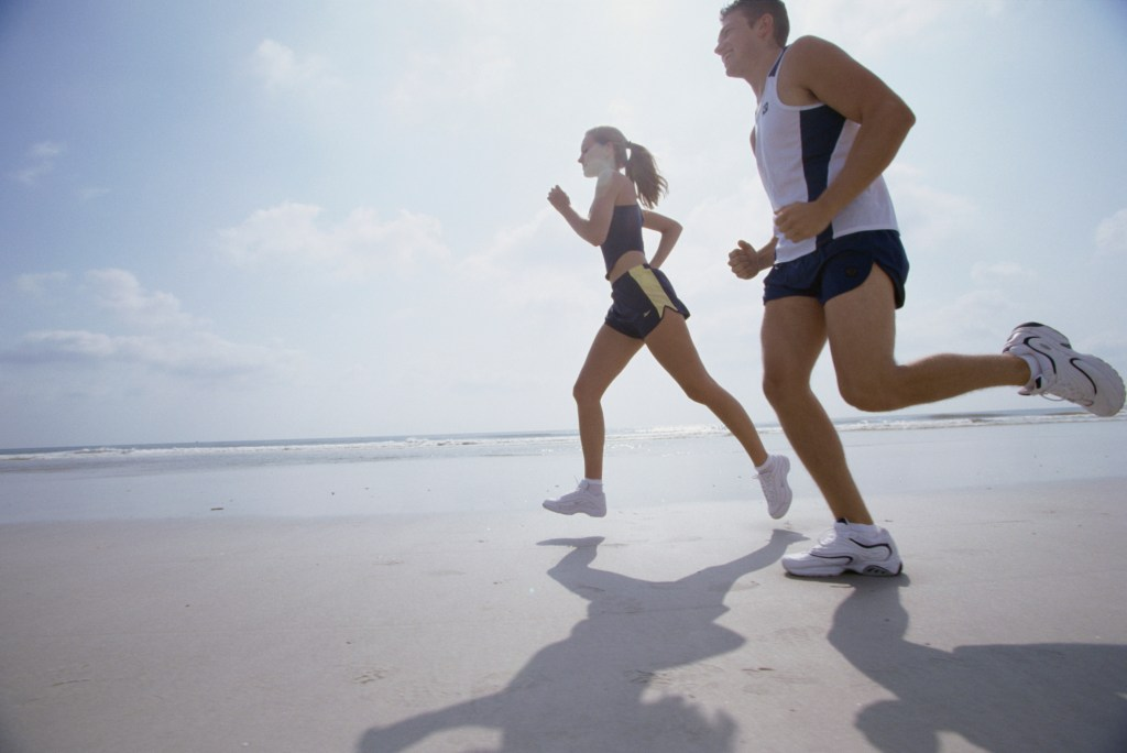 Low angle view of a young couple jogging on the beach