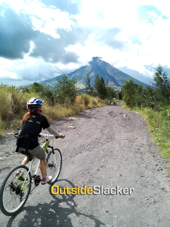 Mountain biker riding to Mayon lava wall