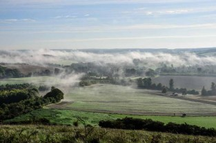 Fast disappearing mist revealing the farm land of the Meon Valley